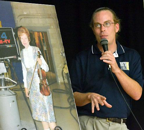 Matt Meinke stands beside a photograph of Ruby Allmond at the 2011 Ruby Allmond contest.