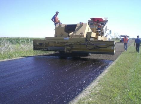 Crews apply seal coating to a North Texas roadway
