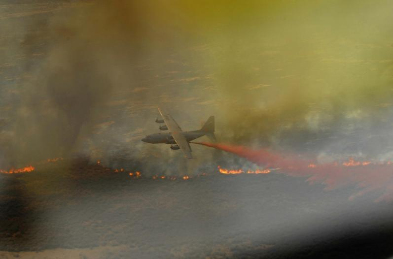 A C-130H Hercules from the 302nd Airlift Wing, Colorado Springs Air Force Reserve, drops a line of fire retardant in West Texas in April 2011.