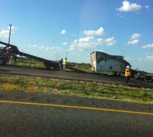 A rig prepares to load a charred trailer on Interstate 30 Wednesday