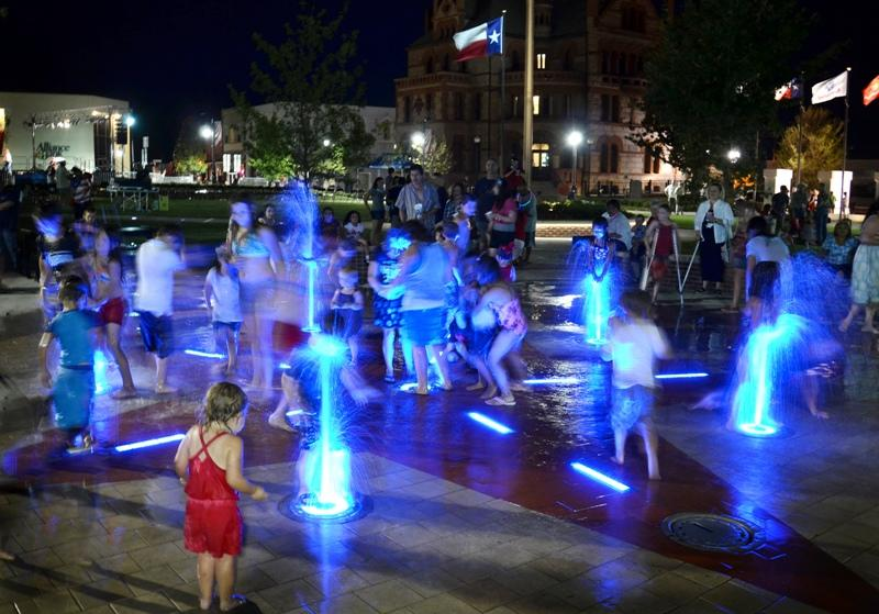 Ultra violet lights illuminate the interactive fountain at night.