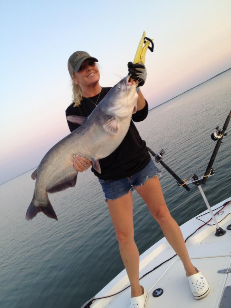 Teri Littlejohn holds up a 32 pound Catfish reeled in by Michael Littlejohn.