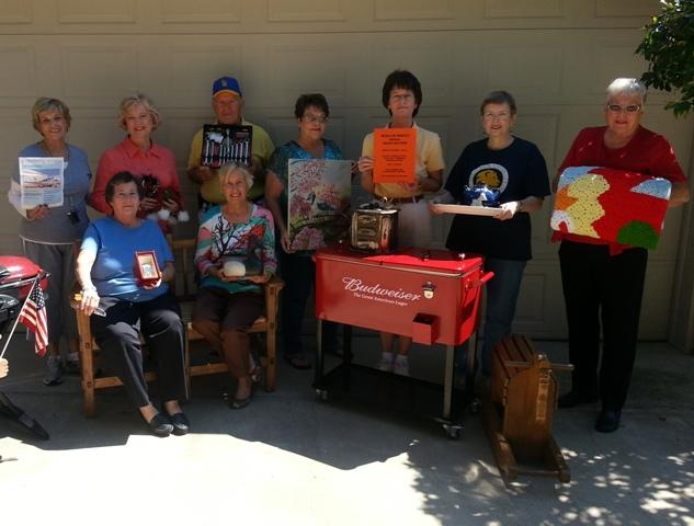 Meals on Wheels Board Members pose with some of the items up for bid Monday