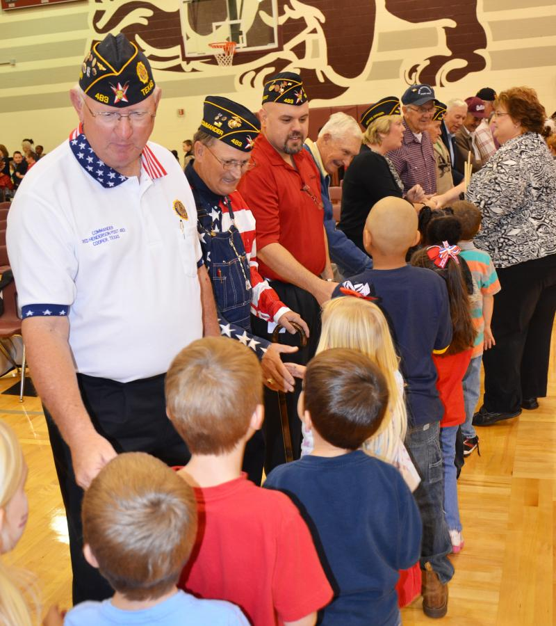 Local Veterans and American Legion Red Henderson Post 483 members Gary Thompson, John Cleveland and J.T. Sokol shake hands with the Cooper students Monday after being honored with a special program.