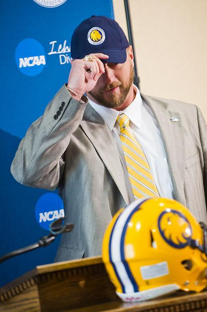 My own kind of hat: Colby Carthel, who wore maroon for seven years as defensive coordinator at West Texas A&M, puts on a blue Texas A&M University-Commerce cap at the annoucement of his hiring as the schools' new head football coach on Tuesday.