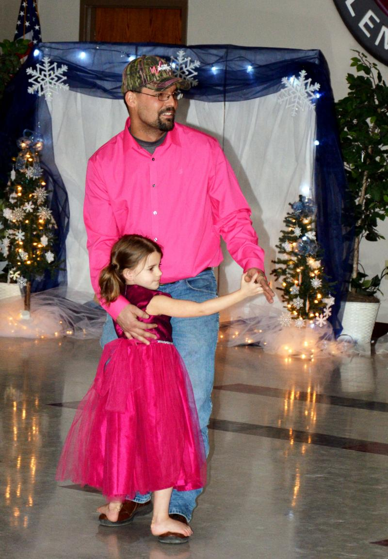 All dressed in pink, Kindal Davis dances on her father Jason's feet during the recent Winter Wonderland Family Dance at the elementary school in Cooper.