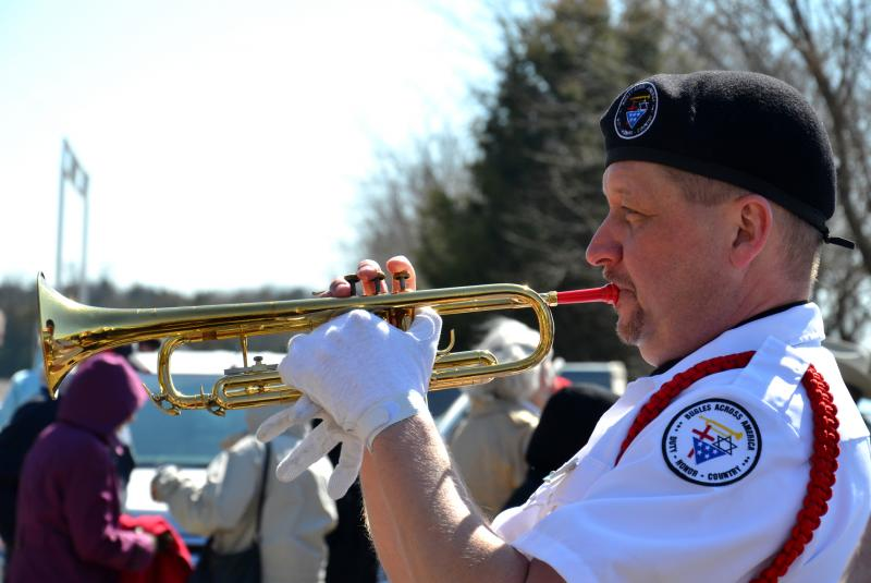 Randall McGuire plays the bugle at the ceremony.