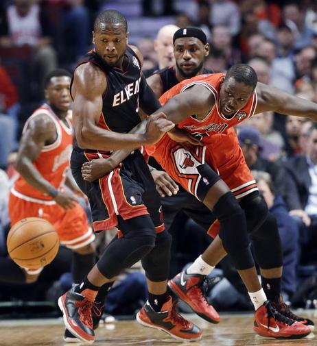 Miami's Dwayne Wade and LeBron James and Chicago's Luol Deng fight for a loose ball in a Wednesday night NBA basketball game. Bulls defeated the Heat 101-97