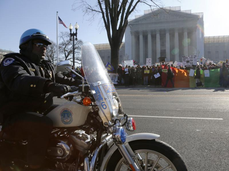 A Washington D.C. motorcycle police officer kept watch on demonstrators outside the Supreme Court Tuesday morning.