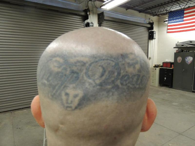 """Drop Dead"" tattooed on the back of Tucker's head"