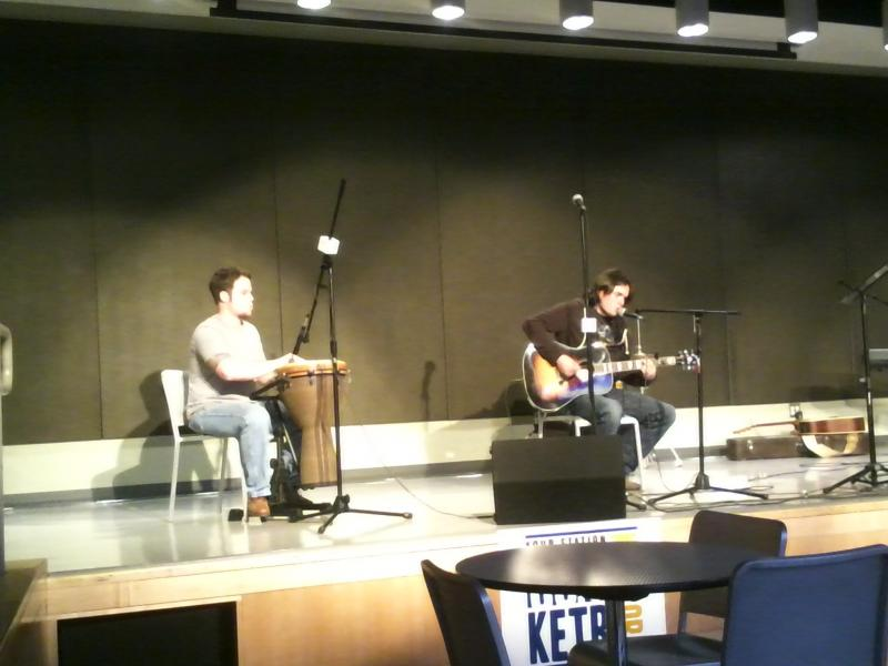 Bryson Moore plays guitar and sings, accompanied by Chase Rippy on the djembe drum, at the Commerce Songwriters Showcase