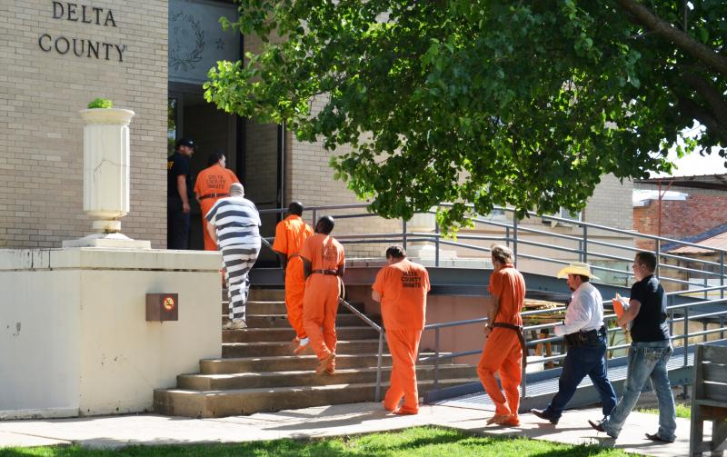 Delta County law enforcement officials lead prisoners into the courthouse on May 1.