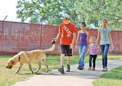 Tristen, Lacey, Sarah and Audrey Burkett of Sulphur Bluff take a walk with their dog Mac in Buford Park