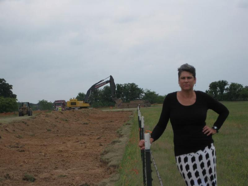 In this undated 2013 photograph, Julia Crawford Trigg stands alongside the fence dividing her property from the area granted to TransCanada.