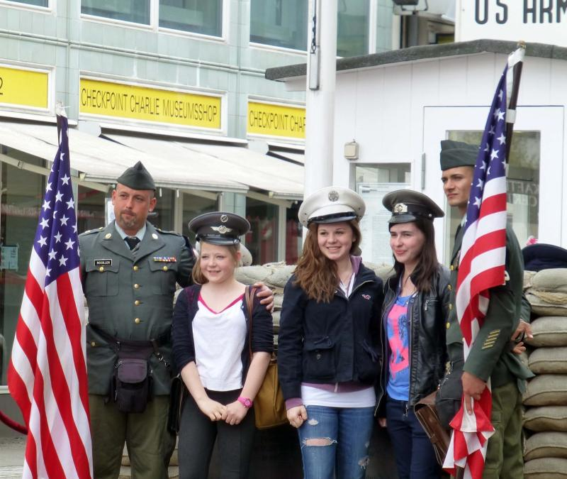 "Tourists pose for pictures with pseudo ""soldiers"" at Checkpoint Charlie"
