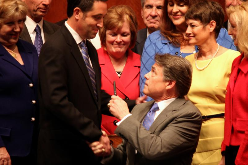 Gov. Rick Perry shakes hands with State. Sen. Glenn Hegar, R-Katy, one of the sponsors of House Bill 2.
