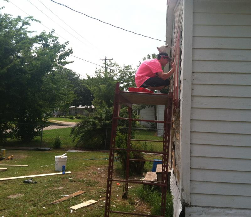 Brice Sechrist works atop a scaffold.