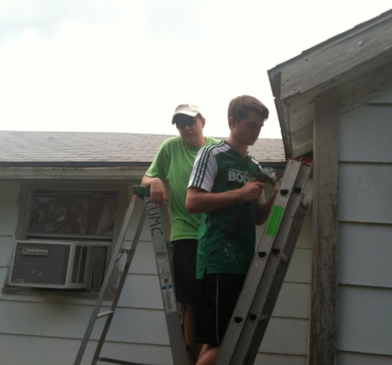 Christopher Vaughan and Jacob Roberts replace an eavestrough.