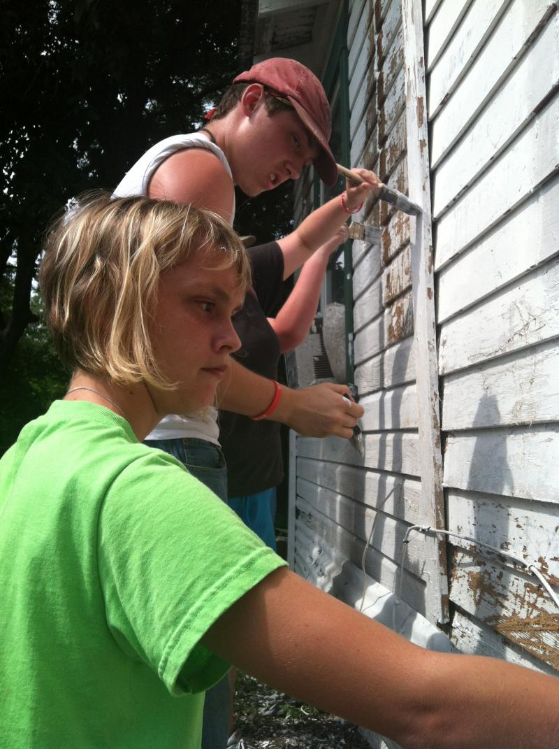 Emily Hughes and Jeff Hodgekiss apply new paint to a house in Commerce.