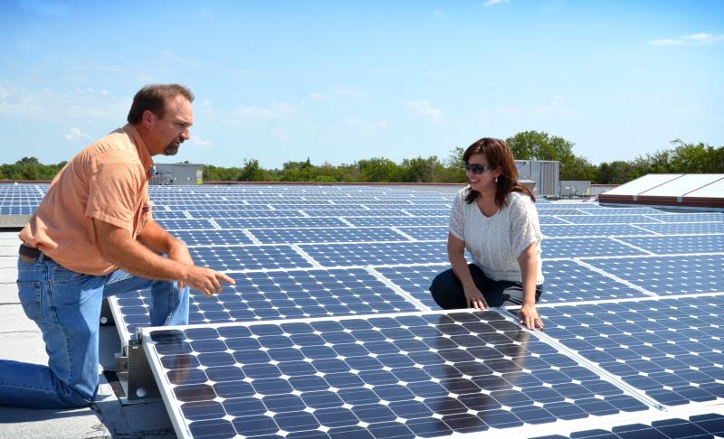 Cooper ISD Superintendent Denicia Hohenberger (on right) inspects the solar panels on the roof of the Cooper Elementary building with Director of School Operations Doug Wicks.