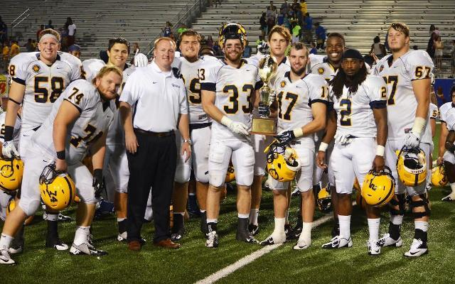 A&M-Commerce's seniors pose with the Chennault Cup following the 41-28 victory over A&M-Kingsville.