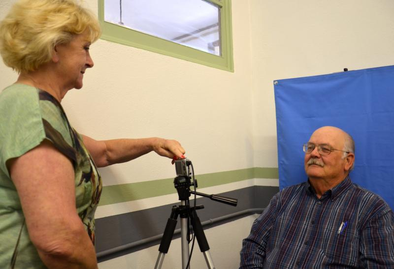 Delta County Judge Herb Brookshire poses for his administrative assistant Sue Hommel as they test the newly acquired camera equipment in order to produce valid Election Identification Certificates necessary for voting.