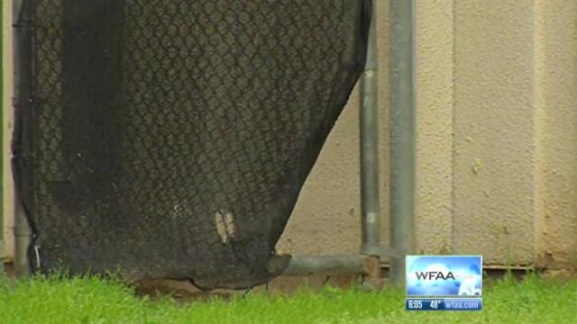 Escape route: This screen shot from WFAA shows the gap in the fence from which two prisoners escaped from the Hopkins County jail's outdoor area in 2013.