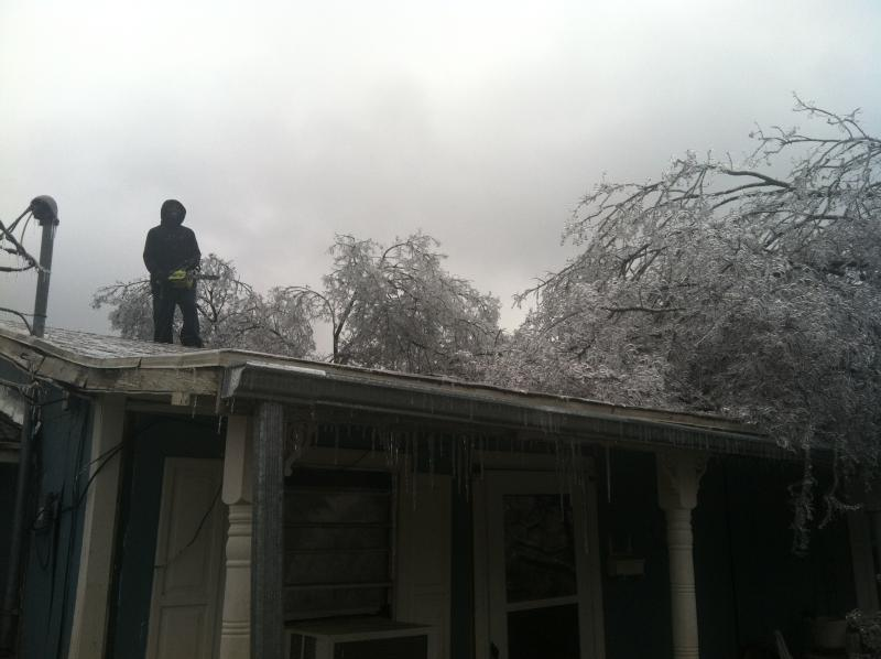 Dante Wade of Commerce took to his roof with a chainsaw to begin removal of the tree that crashed onto his roof and porch on Friday.