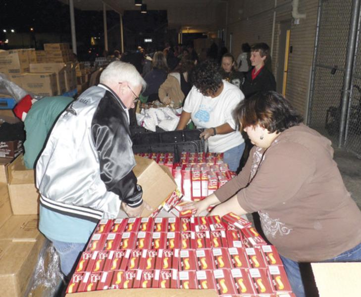 An assembly line of volunteers on the back dock of the GEUS David McCalla building in Greenville had their hands full Wednesday night, preparing hundreds of boxes of food for distribution to needy families through Hunt County Shared Ministries.
