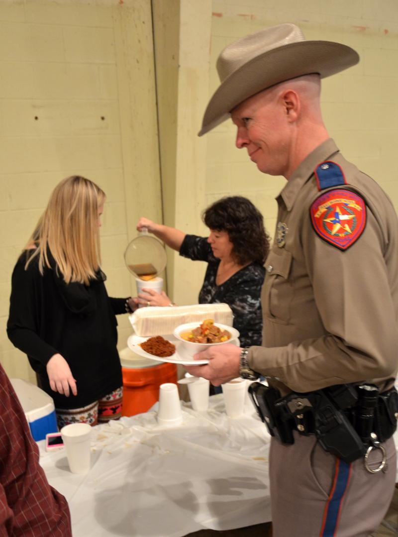 Officer Jamie Blout of Paris looks forward to enjoying a hot bowl of stew while 4-H volunteers prepare his cup of tea. Many law enforcement officers from several surrounding counties showed their support for Game Warden Chris Fried.