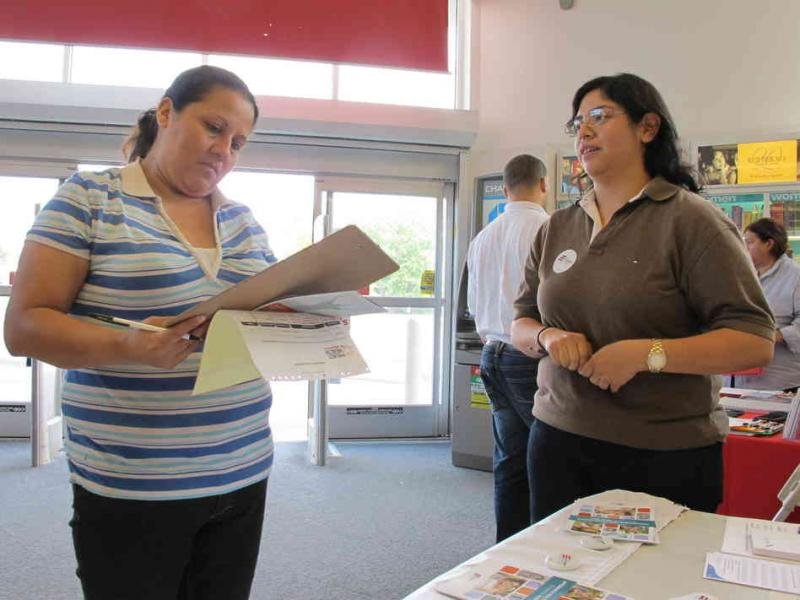 Enroll America outreach worker Rosy Mota (right) talks about the federal health care law with a CVS customer in Houston.
