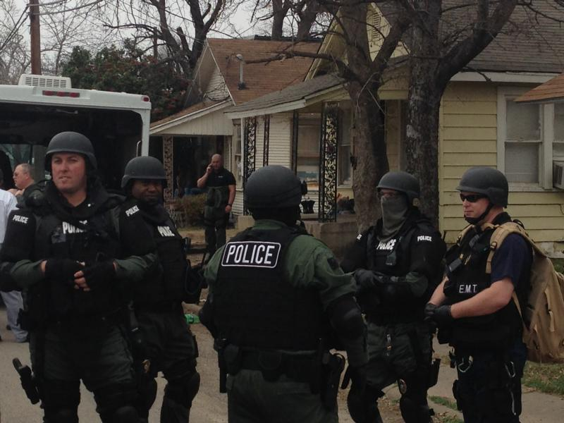 SWAT members gather in front of the residence