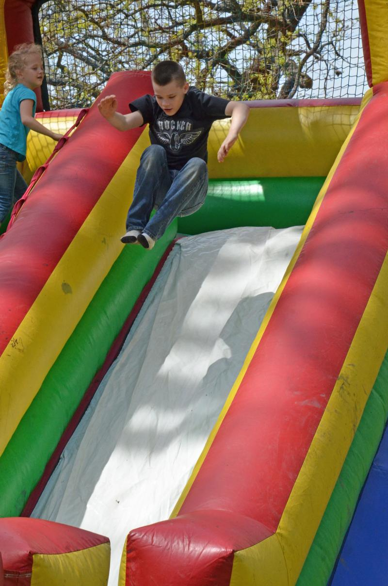 "Children playing in the ""kids zone"" of the fair."