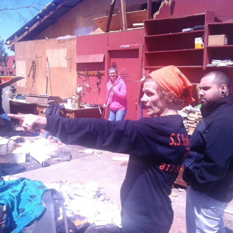 Sheila Krecek shows visitors around the wreckage of her family's property.