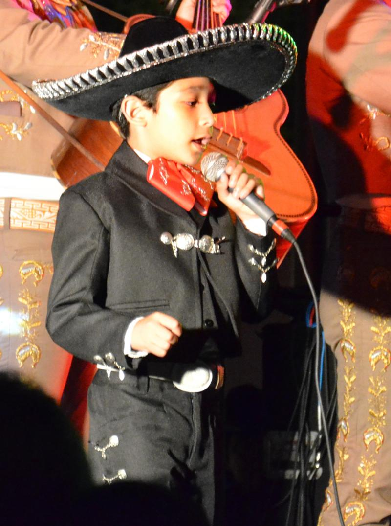 Seven-year-old singing sensation, Christo Escalante, entertains the crowd as he sings with the mariachi band.