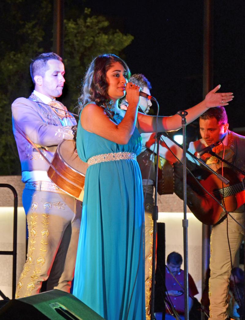 A female singer sing with the mariachi band playing in the background.