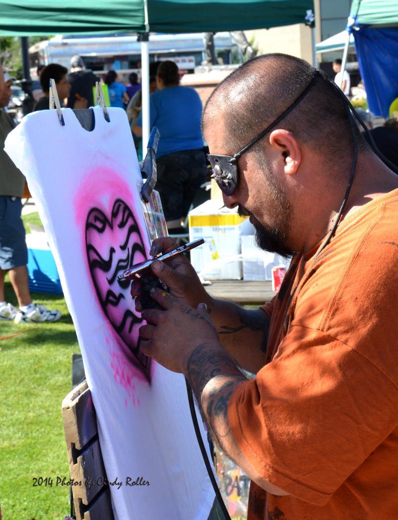 A t-shirt artist draws at the Cinco de Mayo Celebration.