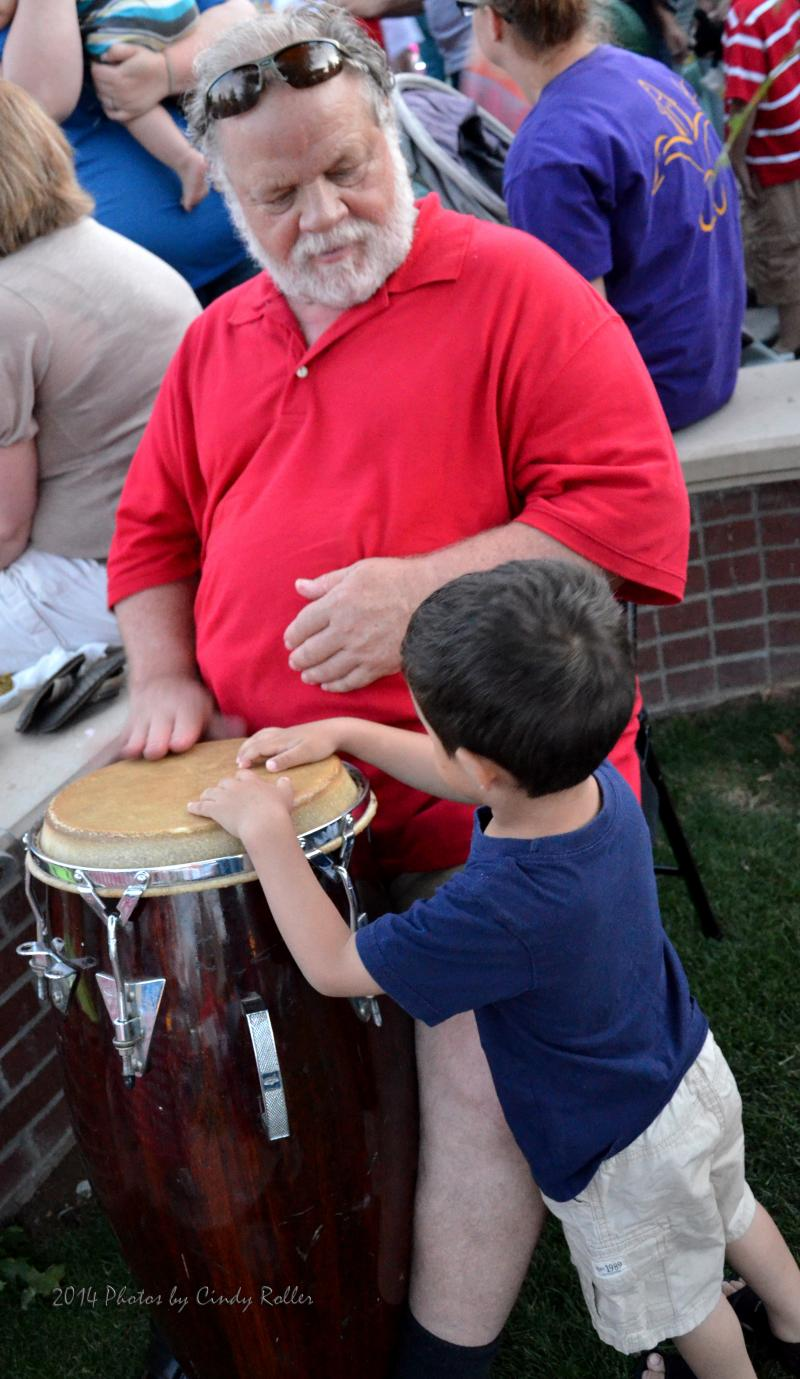 A young boy tries to join the drum circle.