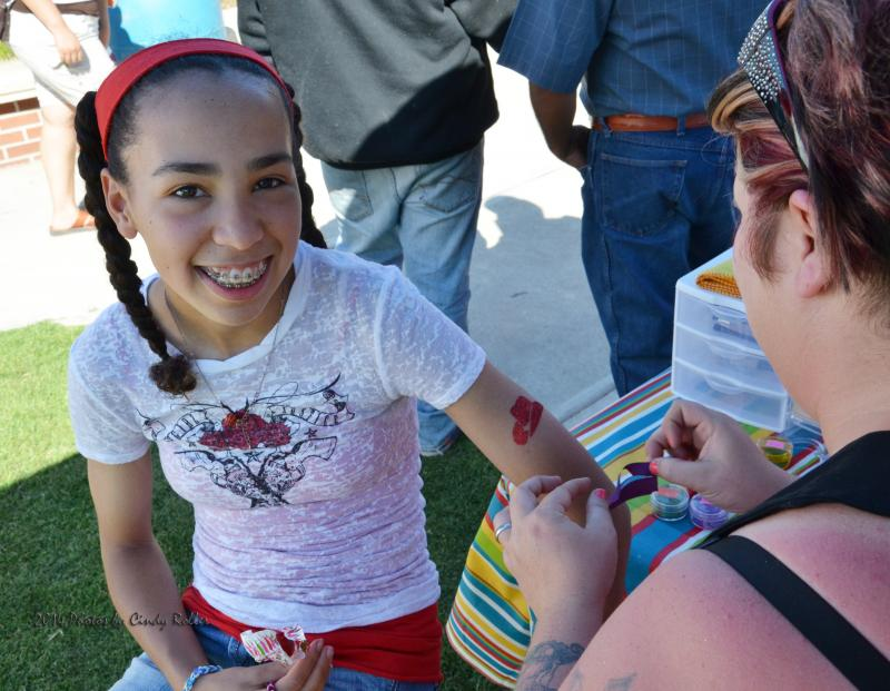 A girl gets a glitter tattoo at the Cinco de Mayo Celebration.