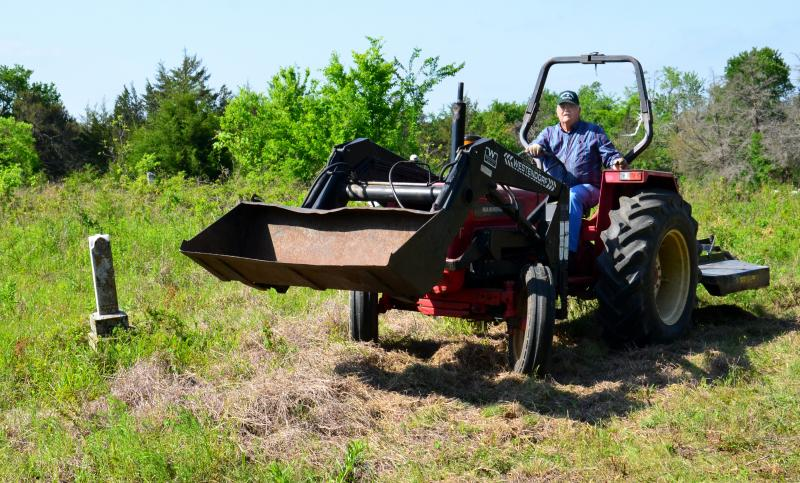 Delta County Judge Herb Brookshire maneuvers his tractor and shredder around the headstones.