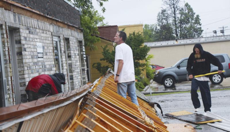 Residents, above photo, help remove the awning which fell from the front of North Texas Title due to the storm on Thursday.