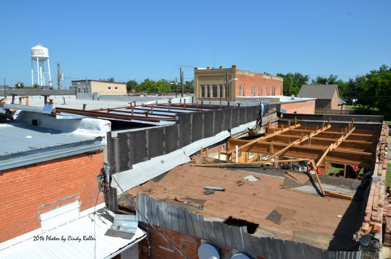 Cooper Outlet's metal roof was pealed away and lies on top of the Professional Land Title Company's roof.