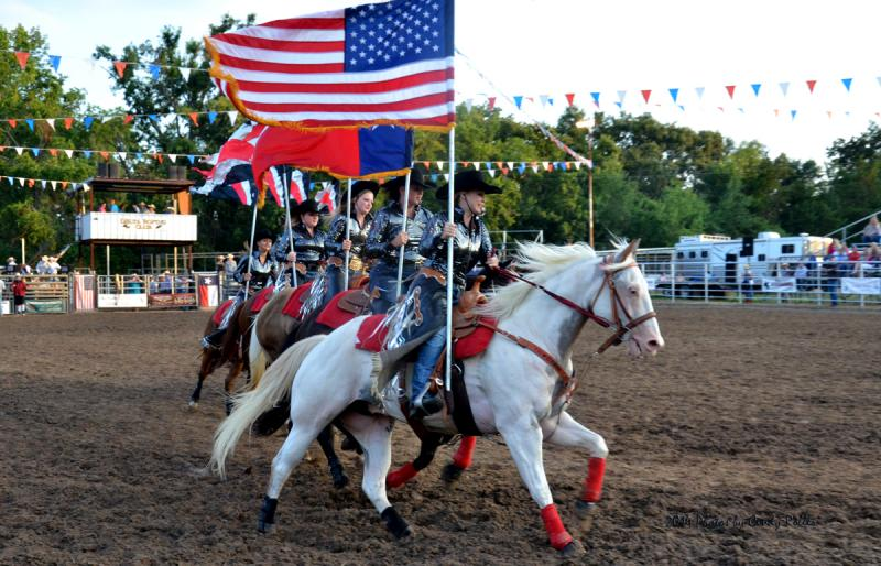 Cowgirls carry the Stars and Stripes and the Lone Star at the 2014 Cooper Rodeo.