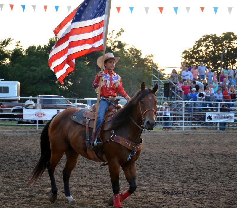Maddison Murray carries the U.S. flag at the 2014 Cooper Rodeo.