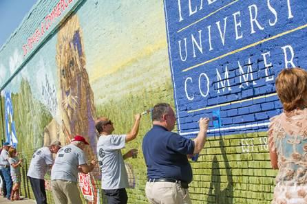 Locals put the finishing touches on the mural at the dedication.