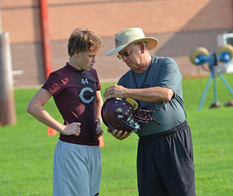 Bulldog Coach Larry Stowers repairs a helmet Monday as the season commences.