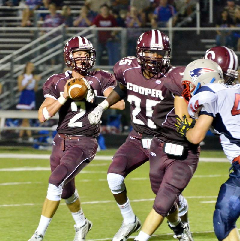 Cooper Bulldog seniors Jadon McGraw (2) is protected by Ira Franklin (25) while preparing to throw his pass.