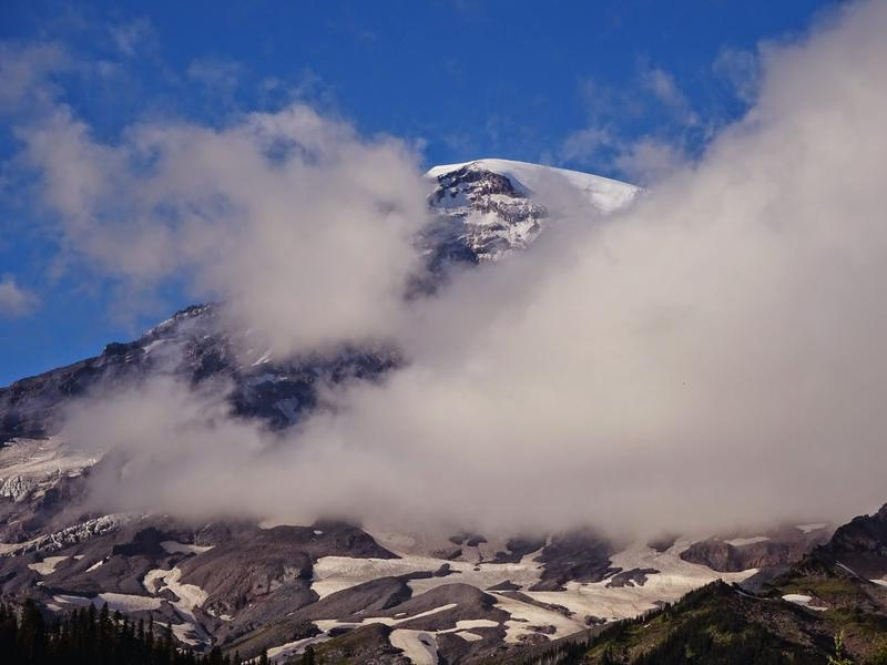 The view of Mount Rainier is revealed though the clouds