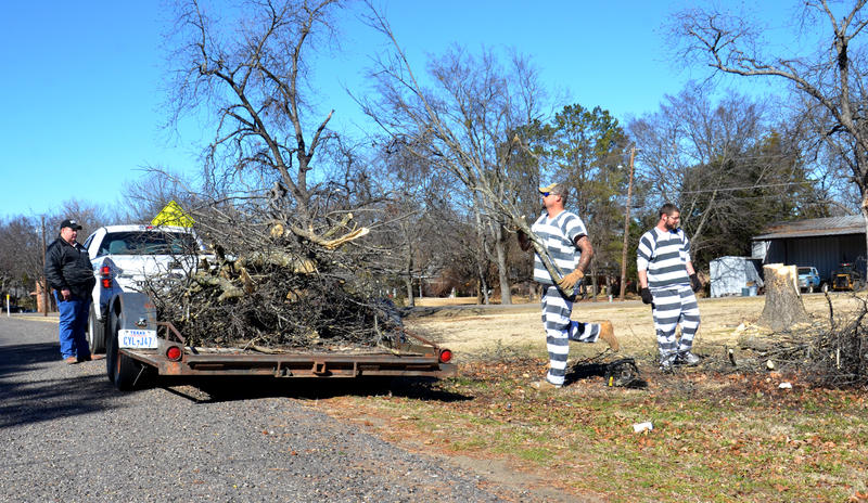 Delta County Sheriff's Deputy Zach Stewart oversees inmates helping beautify the city by hauling off fallen tree branches last year.