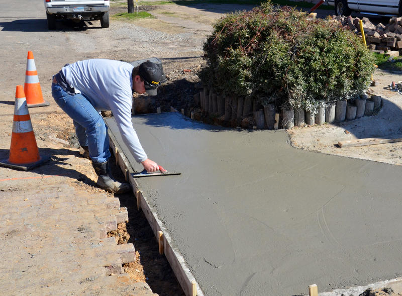 Wesley Scott smooths cement on the northeast side of the Square in Cooper.